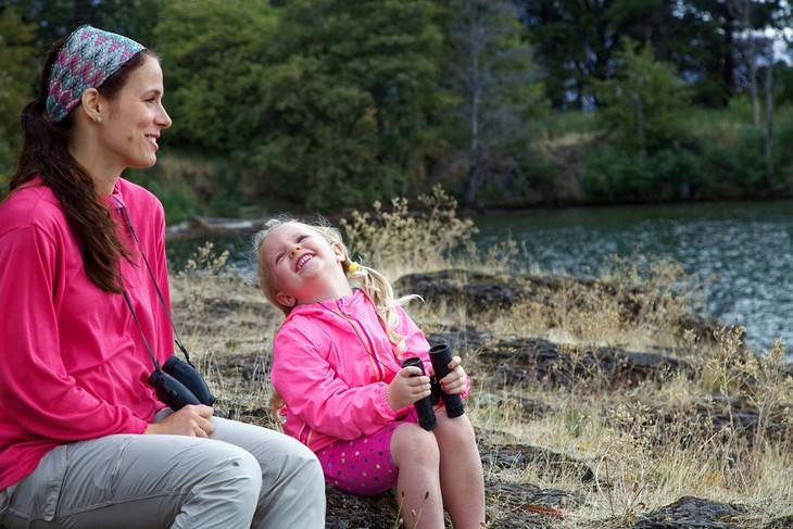 אימא ובת יושבות וצוחקות ליד אגם עם משקפות בידיים