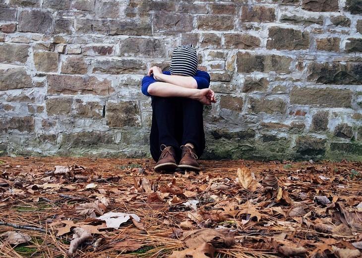 גבר יושב מול קיר כראשו מונח בין ברכיו