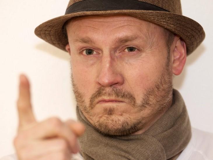 איש עם כובע ופרצוף כועס מרים את האצבע