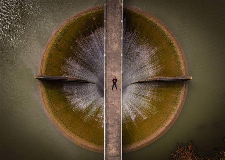 אדם שוכב על גשר מעל סכר