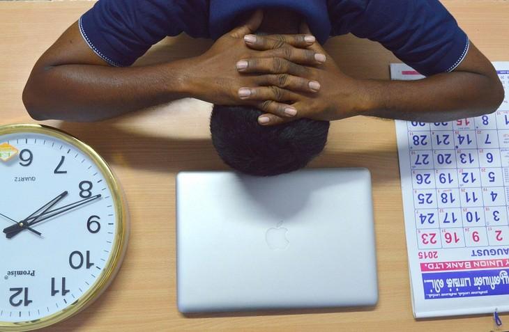 צילום עליון של גבר עם ראש מונח על השולחן כשלצידו לוח שנה ושעון קיר