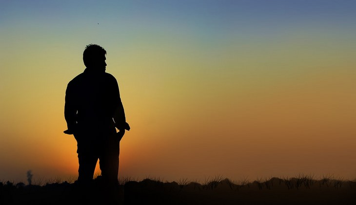גבר עומד מול שקיעה