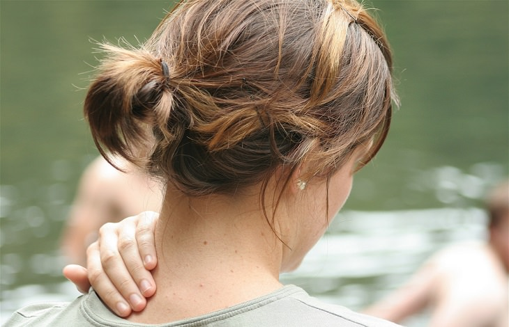 תרגילים למניעת כאבים בצוואר ובגב: אישה מחזיקה את העורף