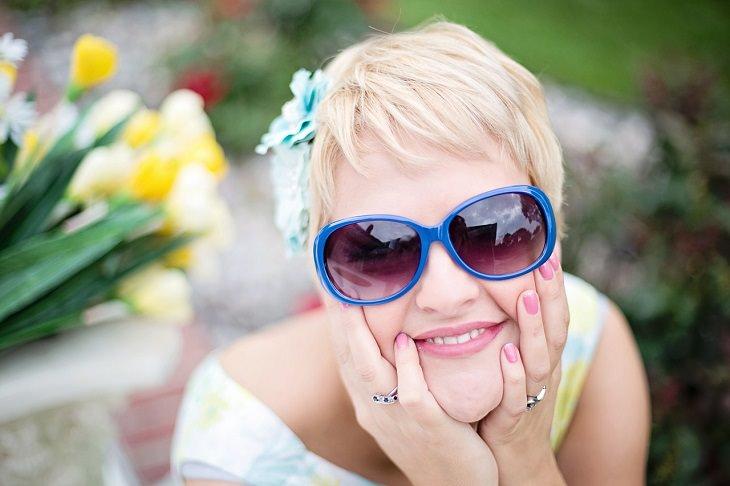 אישה במשקפי שמש מחייכת אל המצלמה