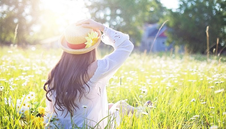 אישה עם כובע יושבת בשדה פורח