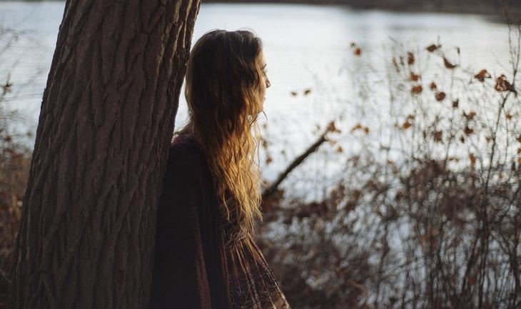 בחורה נשענת על עץ ומביטה אל האופק