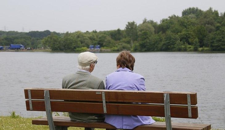 גבר ואישה מבוגרים יושבים ומשוחחים על ספסל