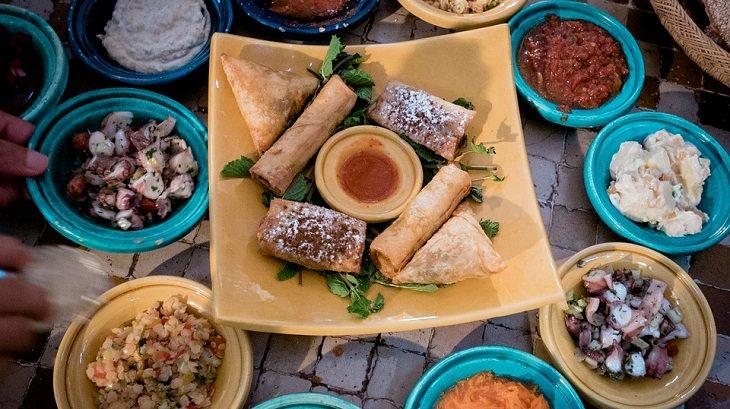 שולחן עם קעריות של מטבלים שונים ושלל מאכלים נוספים