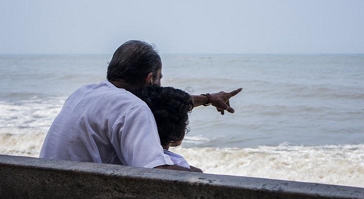 סיבות לאהוב את הגיל: גבר ואישה יושבים מול הים כשהגבר מצביע על הים