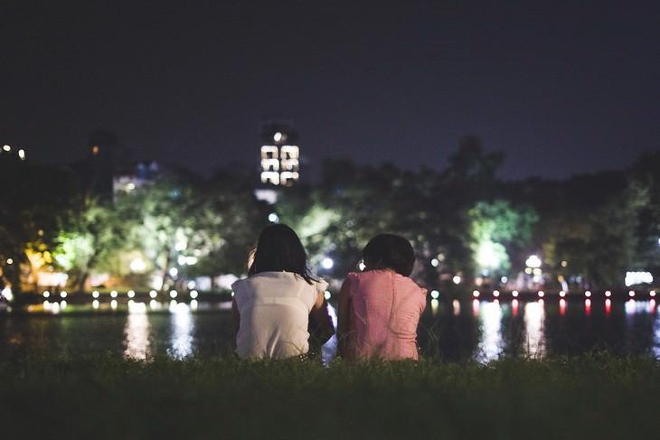 דברים שחשוב לזכור כשאתם חוששים להשמיע את קולכם: שני אנשים יושבים מול אגם בלילה