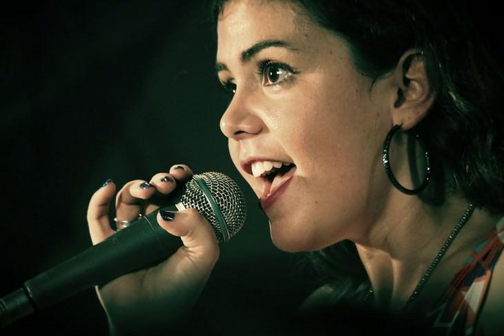 דברים שחשוב לזכור כשאתם חוששים להשמיע את קולכם: אישה אוחזת במיקרופון ומדברת לתוכו