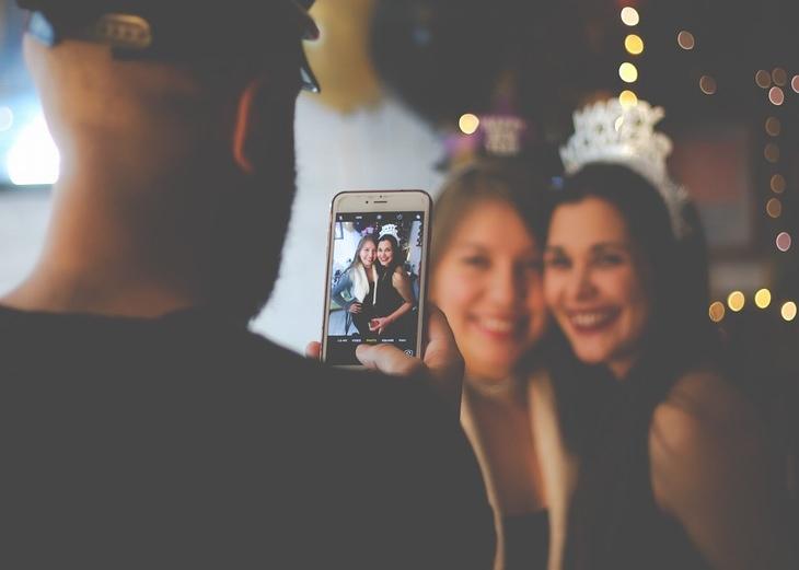 לגרום לבן הזוג לאהוב אותנו: גבר מצלם שתי נשים מחובקות באמצעות הטלפון החכם