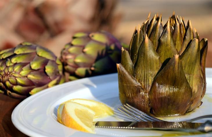 יתרונותיו הבריאותיים של הארטישוק: ארטישוק מבושל על צלחת לצד פלחי לימון