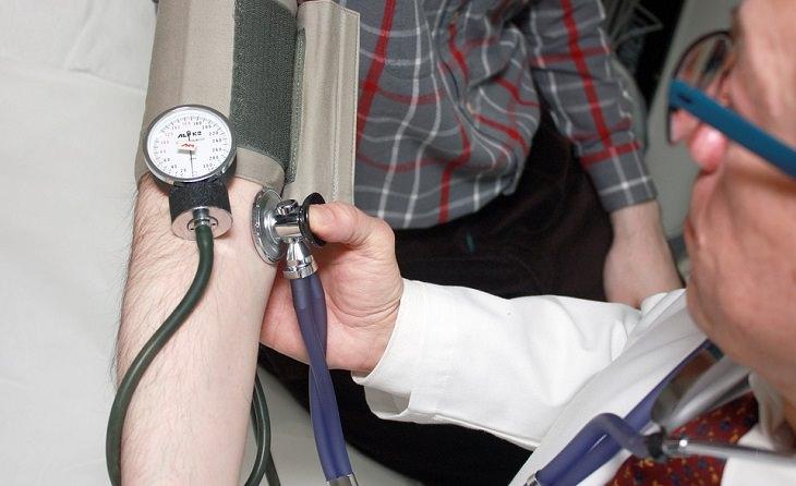 """השיר """"על הנסים"""" מאת דוד אשל: רופא בודק לחץ דם של מטופל"""