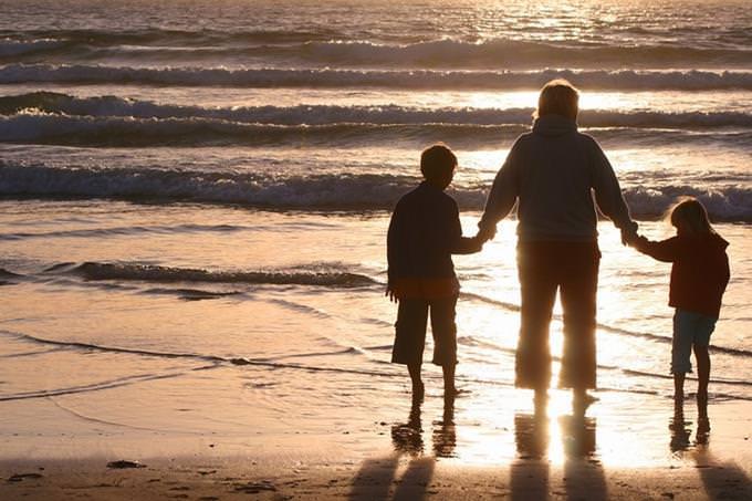 בחן את עצמך - תפקידך במשפחה: אישה אוחזת בידי שני ילדים על שפת הים
