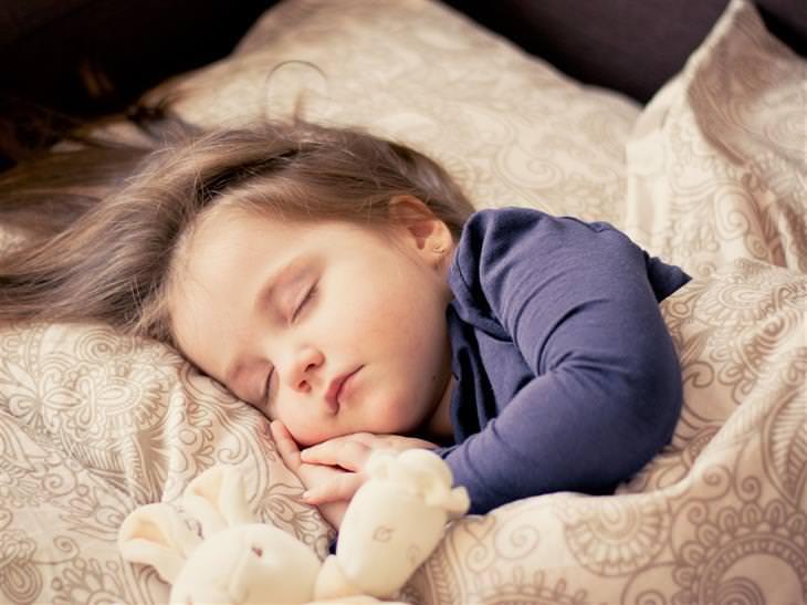 איך להרגיל את הילדים לישון במיטה שלהם: ילדה ישנה עם בובה במיטה