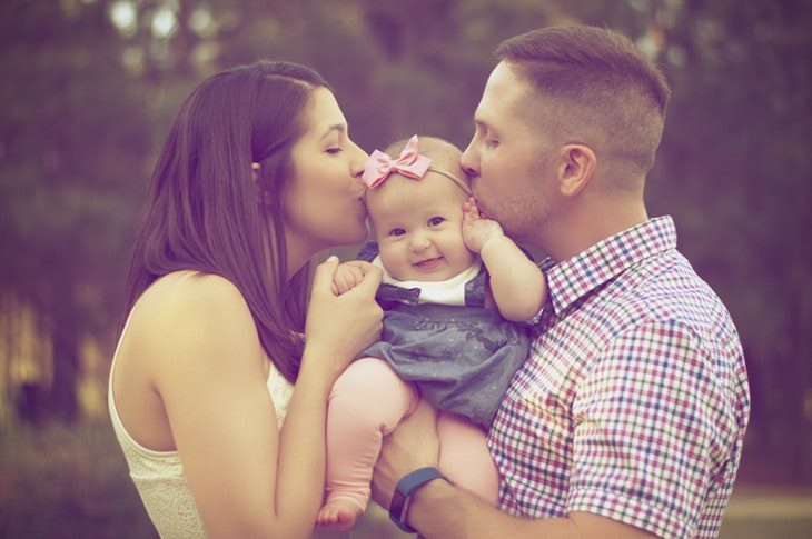 סיבות להודות להורים: זוג הורים נושקים לבתם הקטנה