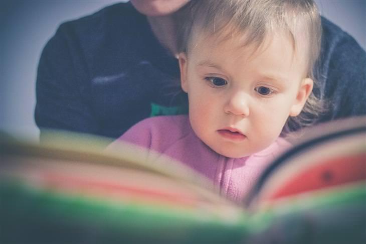 איך להרגיל את הילדים לישון במיטה שלהם: אמא קוראת ספר עם הילדה שלה
