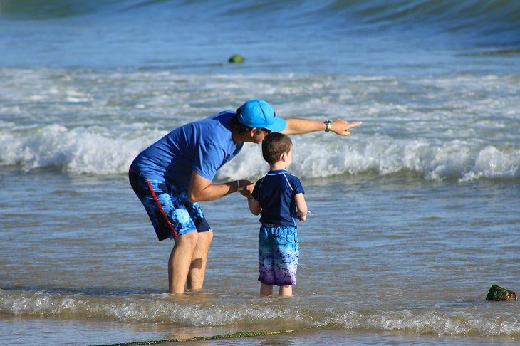 סיבות להודות להורים: אבא עומד עם בנו על שפת החוף ומצביע אל עבר האופק