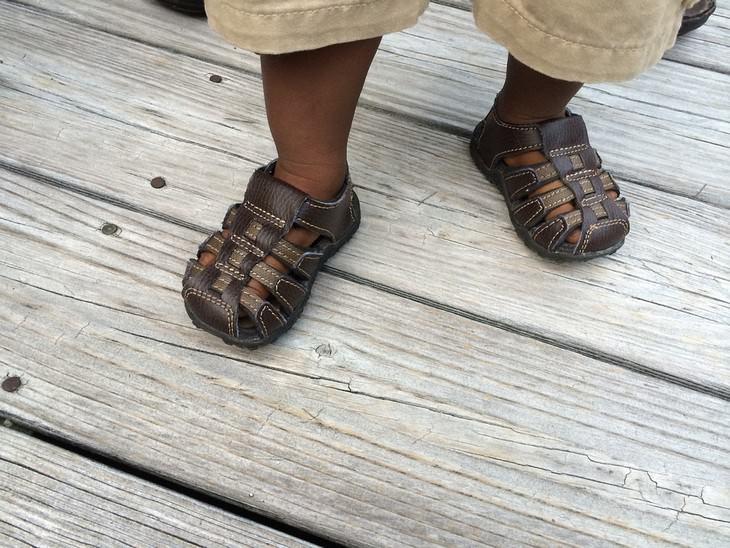 כיצד ללמד פעוטות ללכת: נעליים על רגליים של ילד