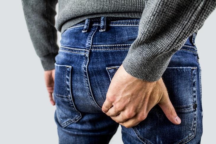 יתרונות בריאותיים של אתרוג: אדם מניח ידיו על אחוריו