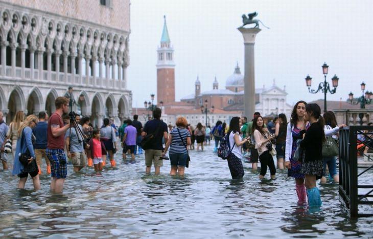 הדברים שצפויים לקרות בעתיד: אנשים עומדים ברחובות ונציה שמוצפת במים