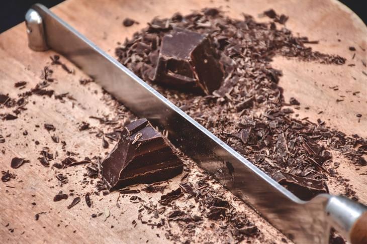 מזונות שמומלץ לצרוך בזמן טיפול באנטיביוטיקה: שוקולד נקצץ על קרש חיתוך