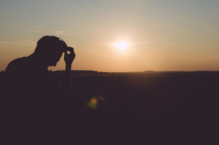 איך להיות ברי מזל בחיים: צללית של איש שכורע ליד שקיעה