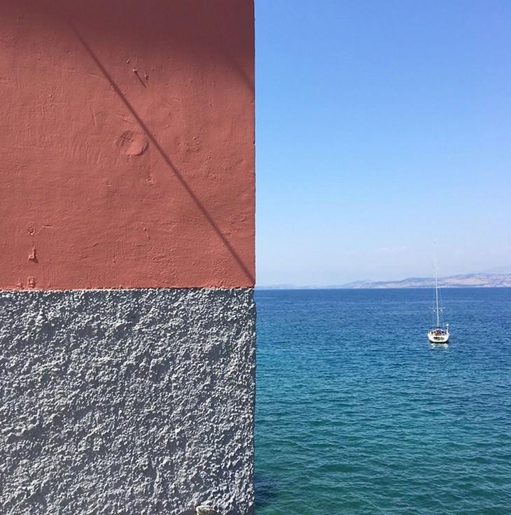 תמונות מדויקות שצולמו ברגע הנכון: סירה שטה על ים שמתיישר עם קו של קיר בשני צבעים