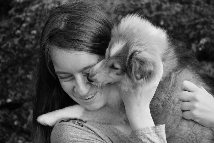 סימנים לכך שהכלב שלכם אוהב אתכם: אישה מחויכת מחבקת כלב