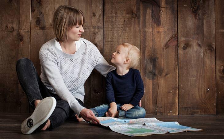טיפים לשיפור תהנהגות הילדים: אמא ובן יושבים על הרצפה ומחייכים אחד לשני