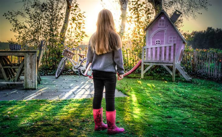 טיפים לשיפור תהנהגות הילדים: ילדה עומדת בחצר האחורית של ביתה מול הזריחה