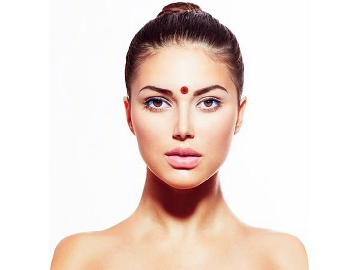 נקודות לחיצה להגברת אנרגיה: פנים של אישה עם נקודה בין הגבות