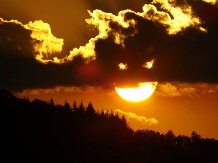 תמונות משעשעות שצריך להסתכל עליהן פעמיים: שמש מוסתרת בחלקה מאחורי עננים ויוצרת תמונה של פה עם שתי עיניים
