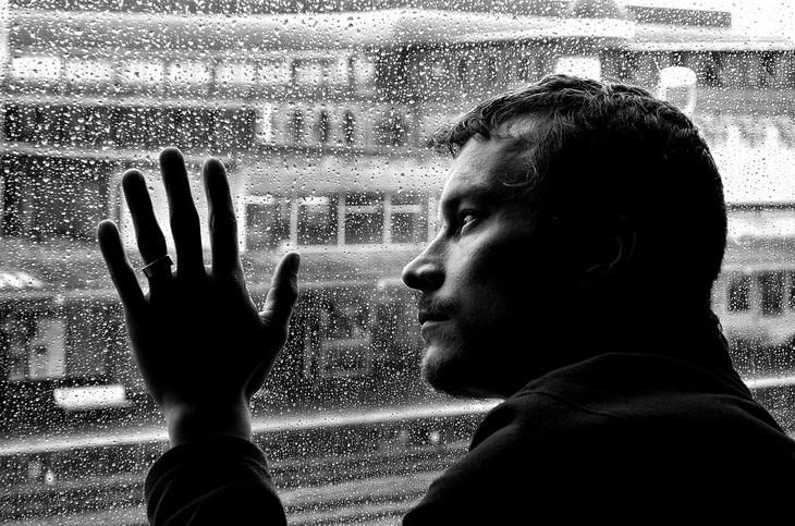סיבות לרעב תמידי: אדם מביט החוצה דרך חלון גשום ומניח את ידו עליו