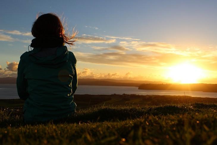 דברים שחשוב לזכור כשדברים נמצאים מחוץ לשליטתכם: אישה יושבת בטבע מול שקיעה