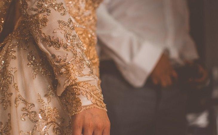 """ציטוטי הרמב""""ם: אישה עם שמלה מעוטרת בחוטי זהב וחרוזים, ברקע עומד גבר"""