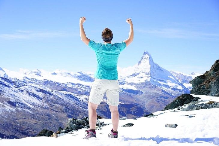 דברים שחייבים להתחיל לעשות: אדם מניף את ידיו על רקע הר מושלג