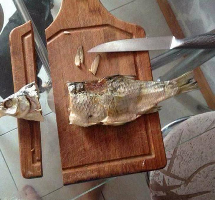 אסונות במטבח:קרש חיתוך עם דג עליו, שראשו של הדג חתוך, יחד עם הקרש שתחתיו