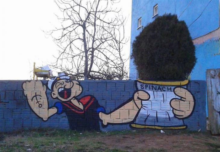 """יצירות גרפיטי שמשדרגות את הרחובות: גדר שעליה מצויר פופאי, ומאחורי """"פחית התרד"""" שלו יש שיח שנרא כאילו יוצא ממנה"""