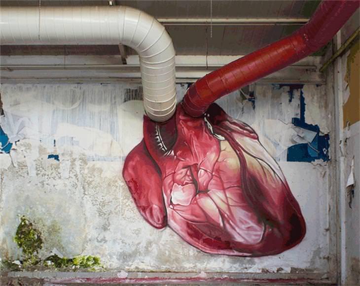 יצירות גרפיטי שמשדרגות את הרחובות: צינור אדום וצינור לבן נכנסים לקיר, היכן שיש ציור של לב, כך שהם נראים כמו כלי דם