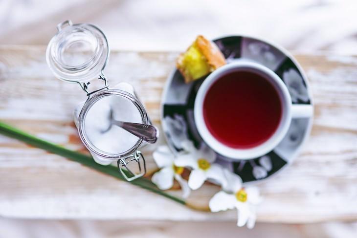 גמילה מסוכר ב7 צעדים: צילום עילי של כוס תה עם צנצנת סוכר לידה