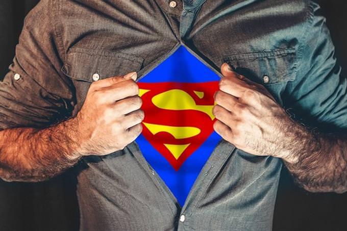 אדם חושף חולצה שעליה הסמל של סופרמן