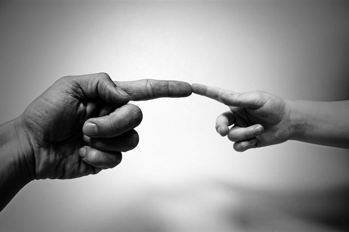 יד של ילד ויד של מבוגר מפגישות אצבעות