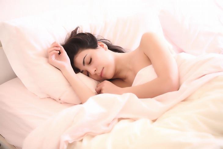 נזק של שינה עם שיער רטוב ומניעתו: אישה רדומה שוכבת במיטה, עטופה בשמיכה