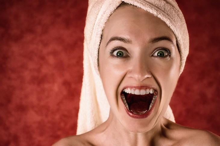 נזק של שינה עם שיער רטוב ומניעתו: אישה עם מגבת סביב שיערה מביטה בפליאה
