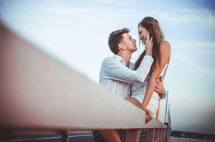ארבעת סוגי האוהבים: גבר מלטף אישה שיושבת על מעקה של גשר