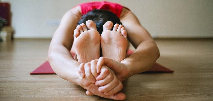 תנוחות מומלצות על ידי מומחי יוגה: אישה רוכנת קדימה ואוחזת בכפות רגליה