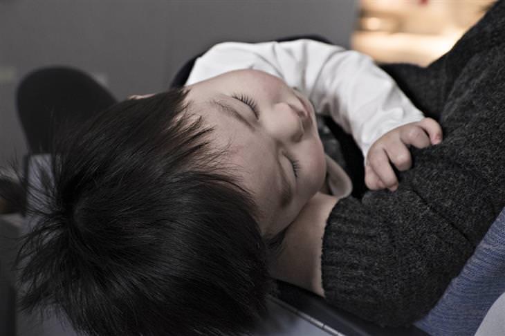 סימנים לדלקת קרום המוח אצל ילדים: פעוט ישן בידיים של הוריו