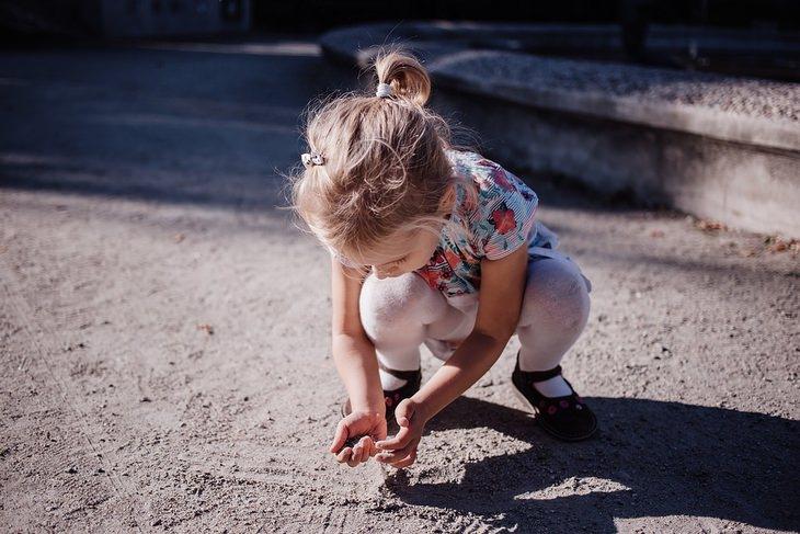 תרסיסים משמנים אתריים: ילדה משחקת בידייה בחול ברחוב